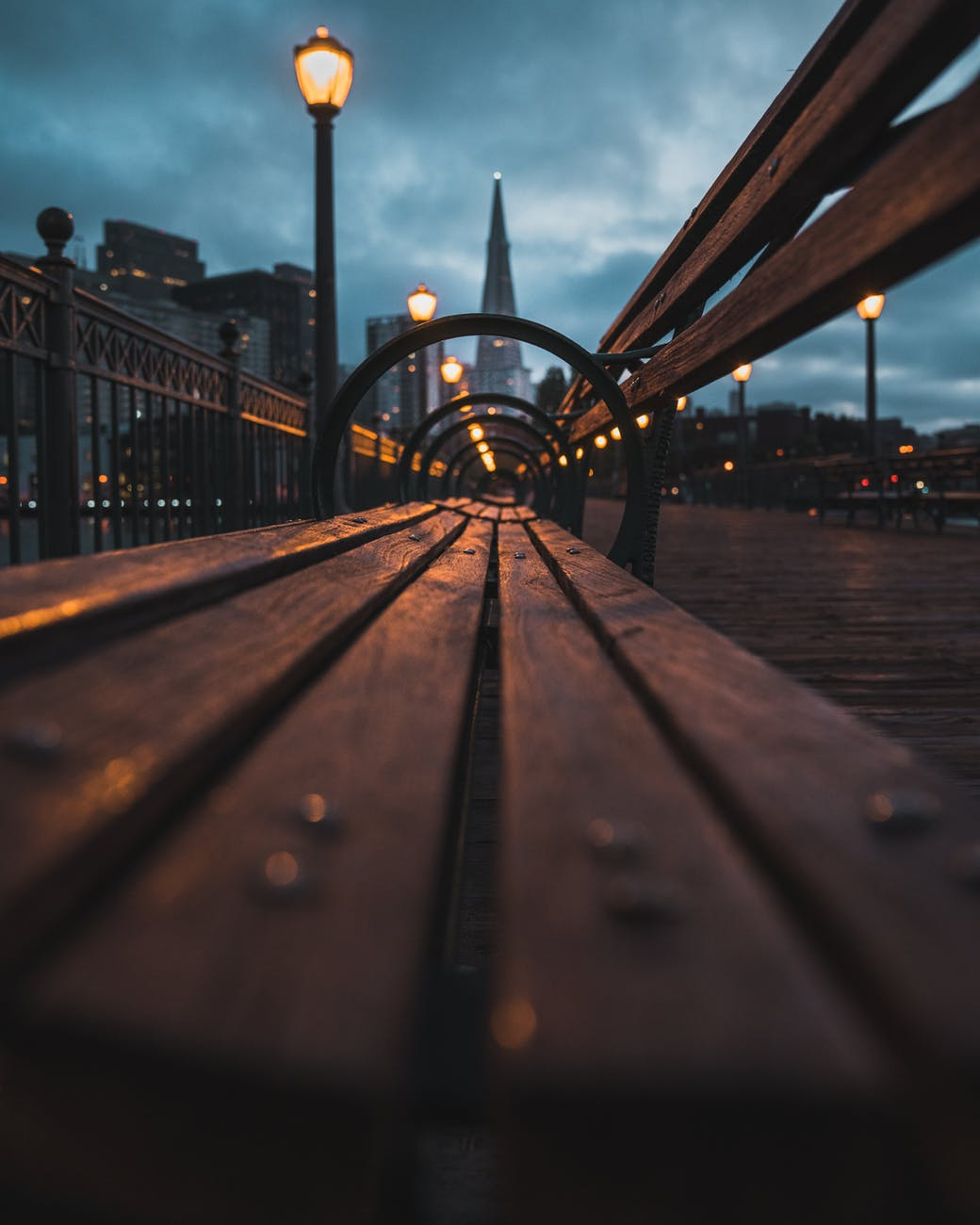 closeup photo of wooden bench near the lamp post during night time
