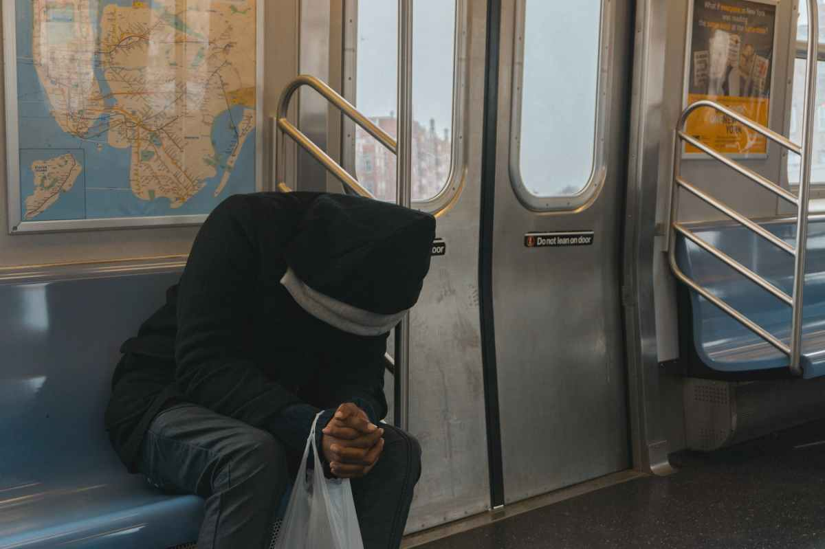 person in black hoodie sitting on train bench