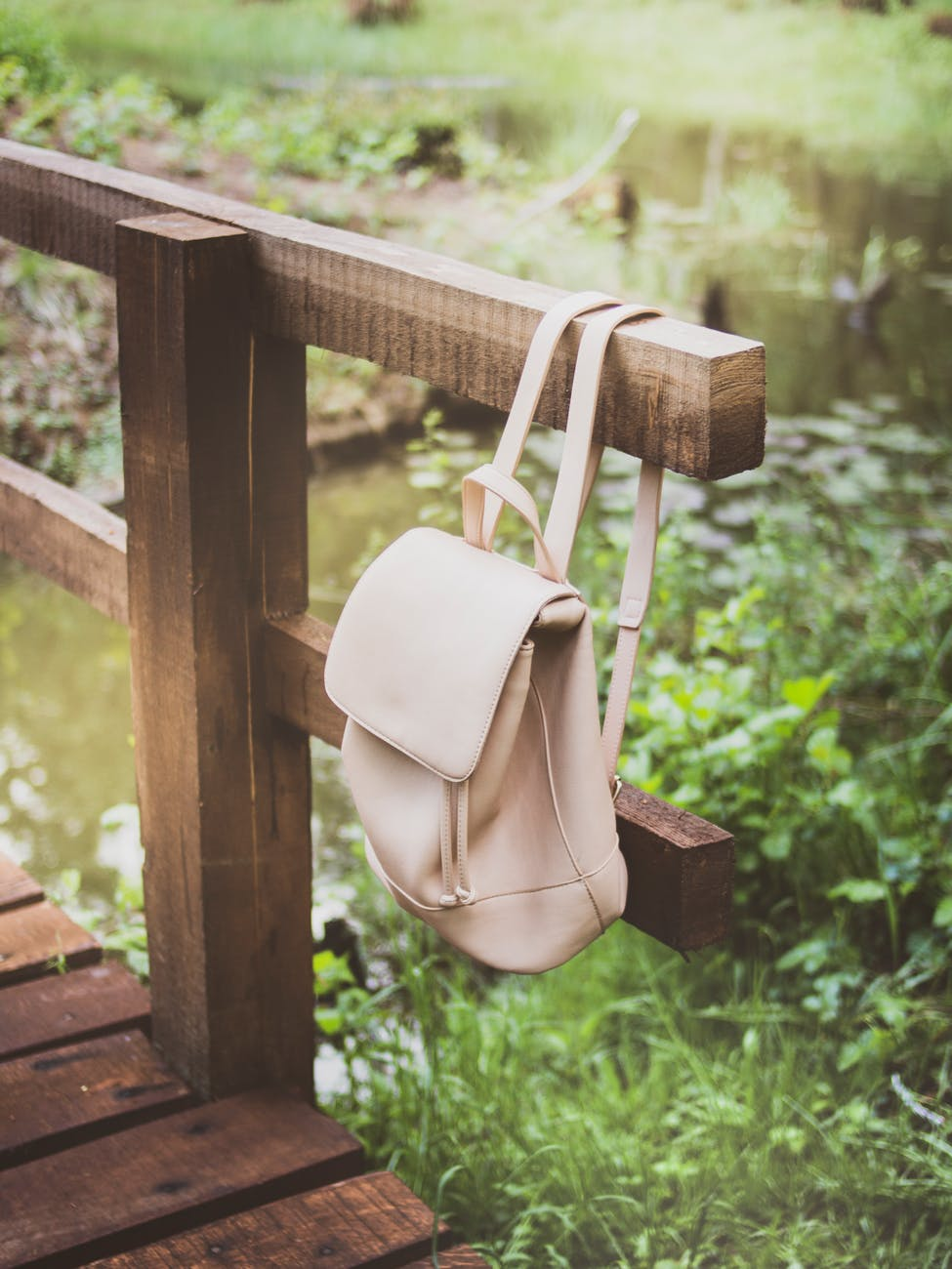 white backpack hanging on wooden bridge